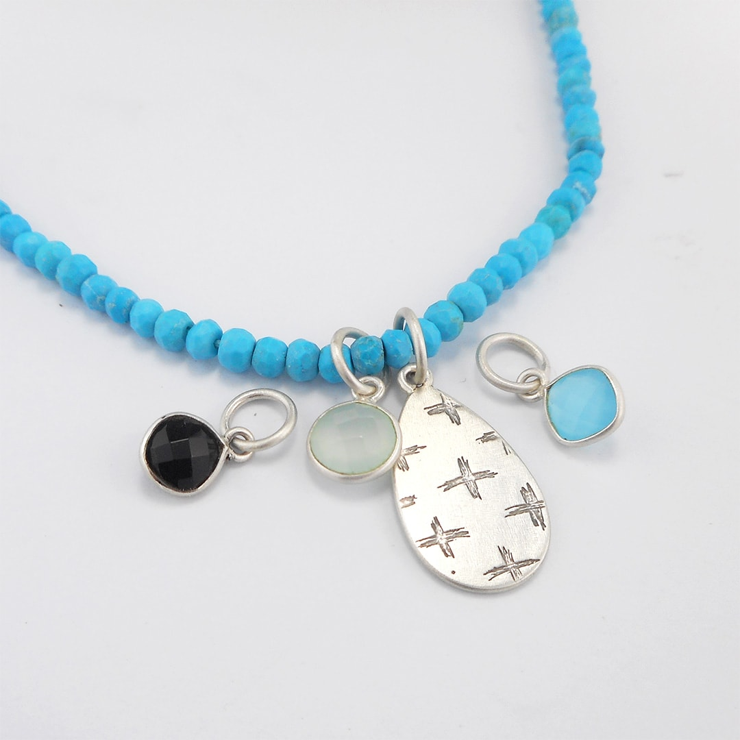 turquoise necklace with patterned silver pendant and gemstone drop
