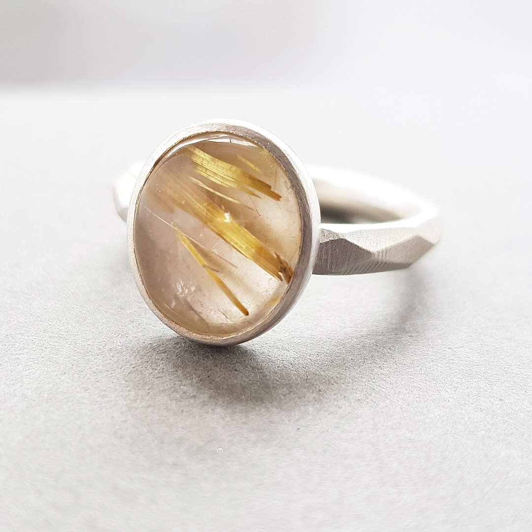 Golden rutile quartz on faceted silver band
