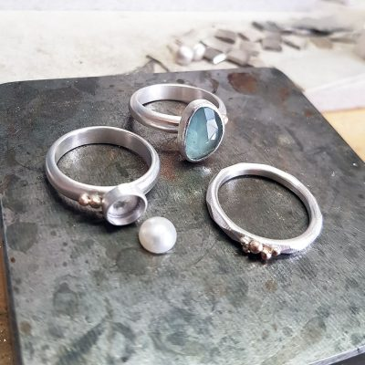 custom made silver stacking rings with aquamarine. freshwater pearl and 9ct yellow gold