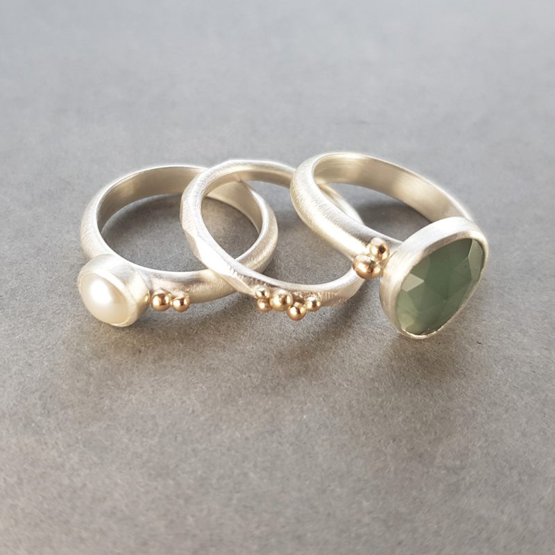 Aquamarine and white pearl stacking rings in brushed silver with gold accents