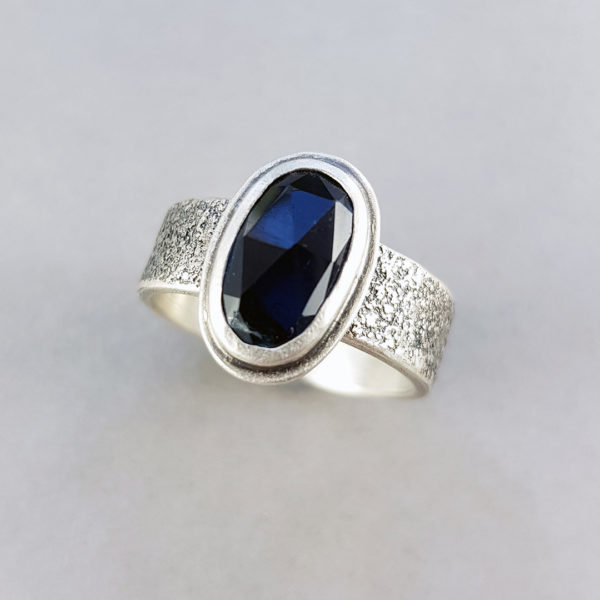 Dark blue rose cut Tourmaline on a textured silver band ring