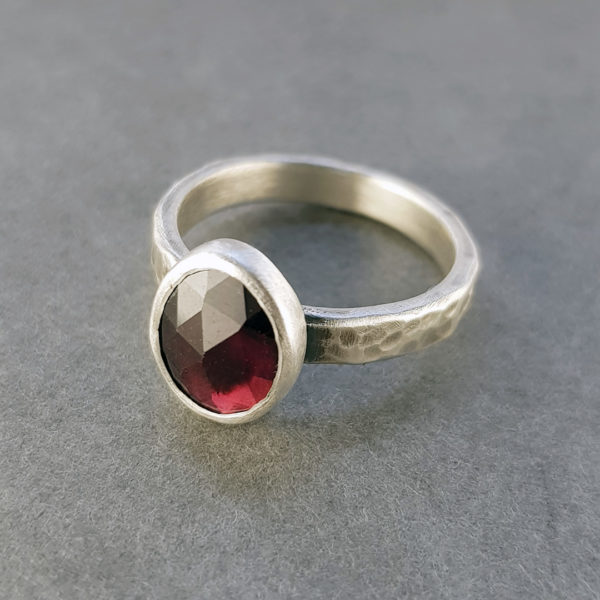 Red garnet and silver ring with hammered band