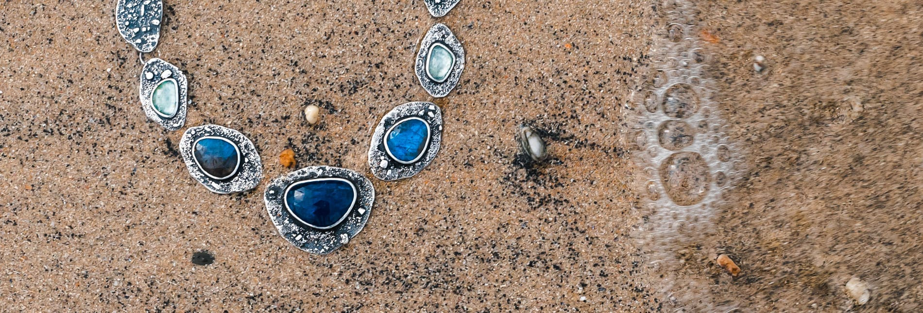 Rugged statement necklace in the sand at the beach