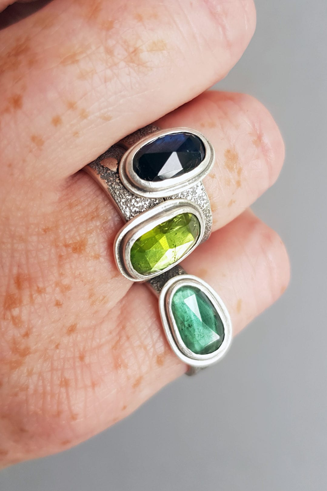 Green and blue tourmaline rings in textured silver on hand