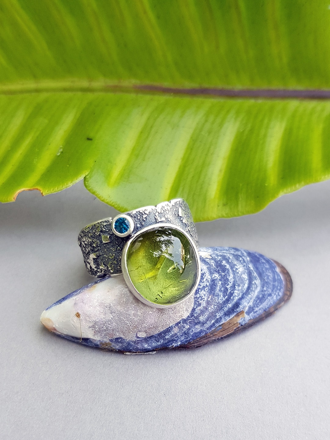 Green tourmaline and blue topaz ring in textured sterling silver
