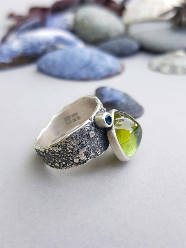 Side view of tourmaline and topaz ring in silver