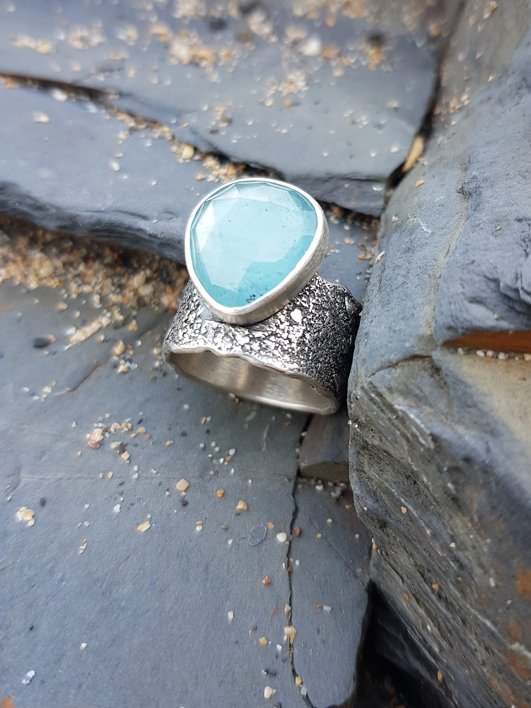 Aquamarine and textured silver ring on the rocks at the beach, Cornwall