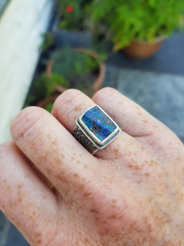 Boulder opal ring on hand