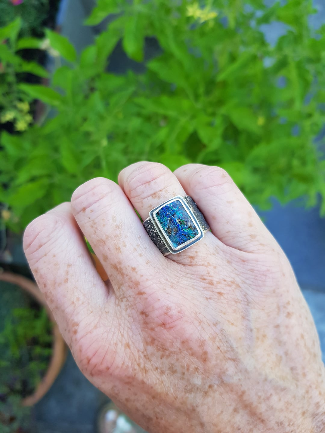 Boulder opal ring on finger and a bit of gardening
