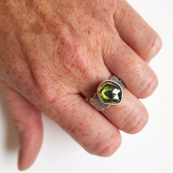 Green and brown tourmaline sterling silver ring on hand