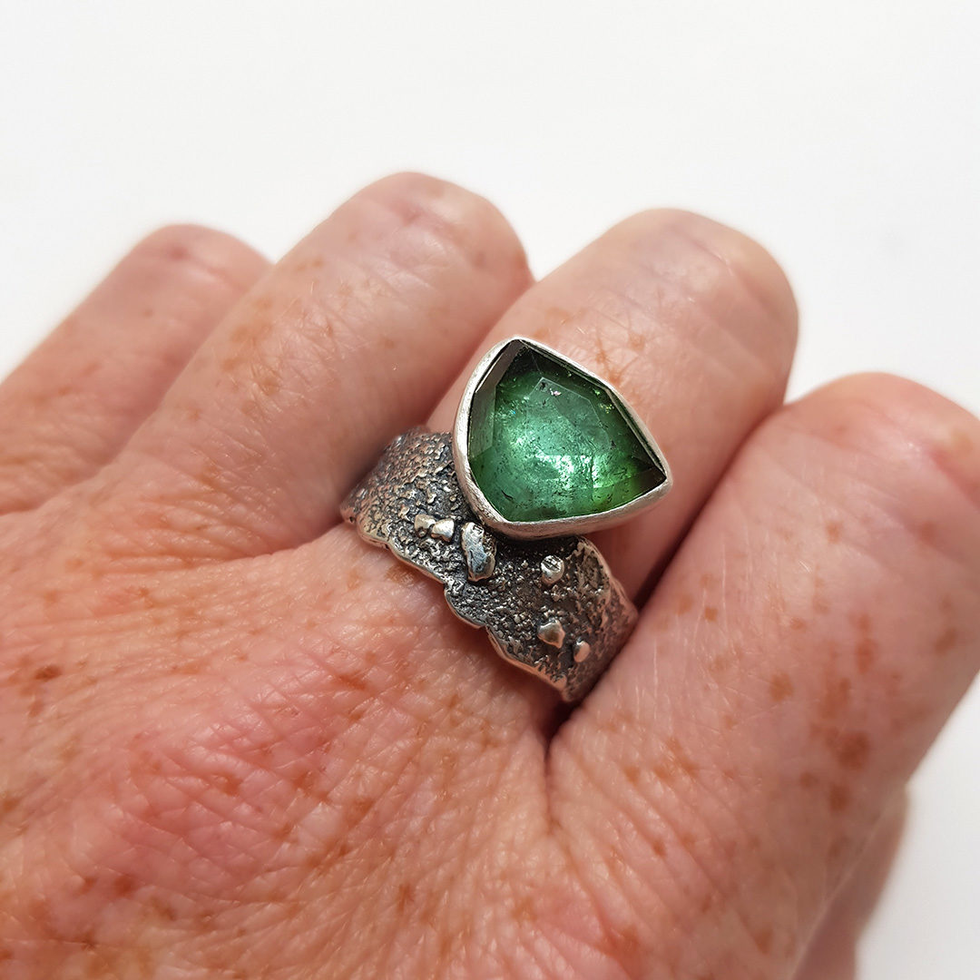 Shaded green tourmaline ring on textured sterling silver band
