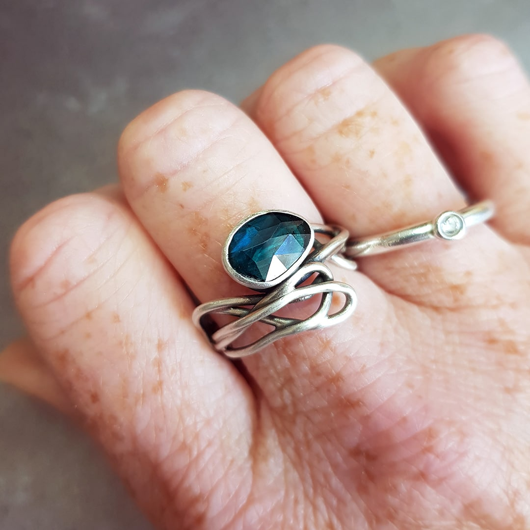 Teal blue tourmaline stone set on a tangled sterling silver band