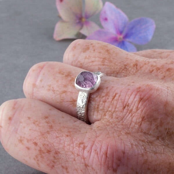 Pink Tourmaline gemstone and silver rings on a hand