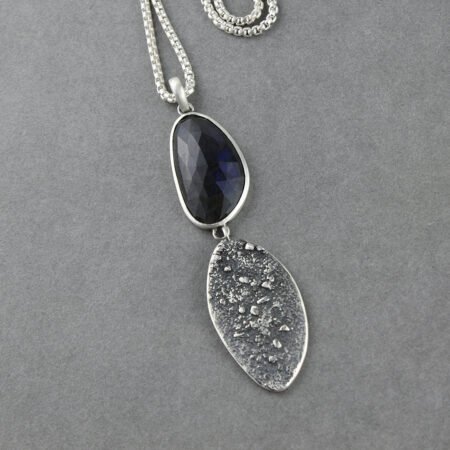 Labradorite gemstone pendant in textured sterling silver hung on a long chain