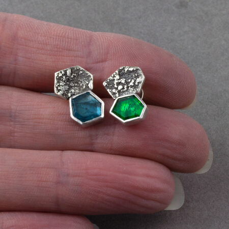 Emerald and kyanite stud earrings in textured sterling silver in hand