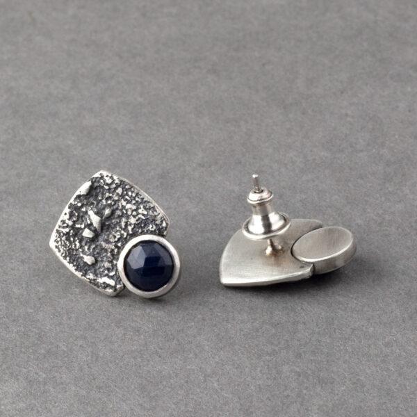 Backs of blue sapphire stud earrings in textured sterling silver