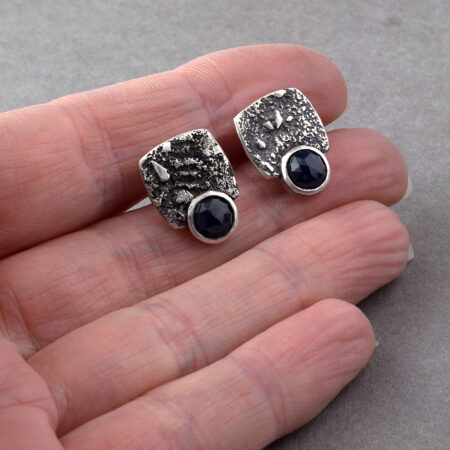 Blue sapphire stud earrings in textured sterling silver in hand