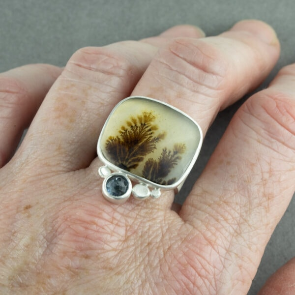 Dendritic agate and aquamarine ring on hand for scale