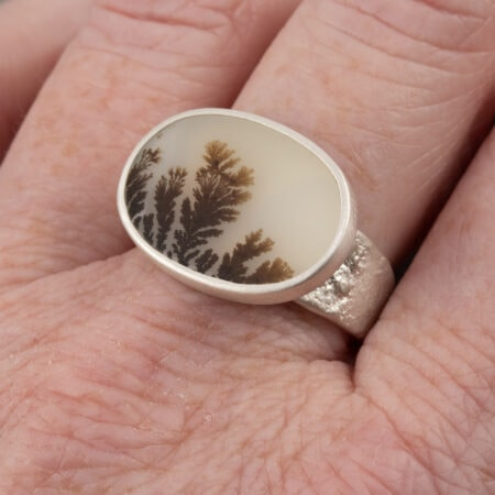 Dendritic agate ring on hand