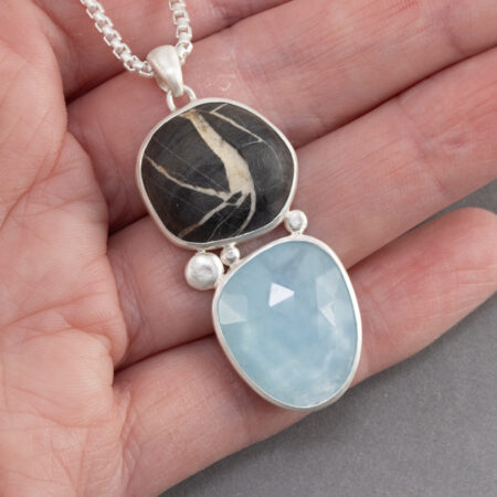 Holding a aquamarine and beach pebble pendant