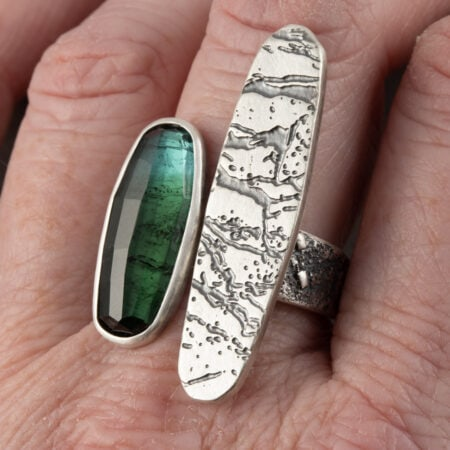 Blue-green tourmaline and sterling silver ring worn on finger