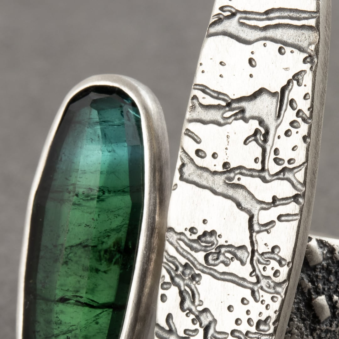 Closeup of Shaded blue-green tourmaline ring with slate pattern
