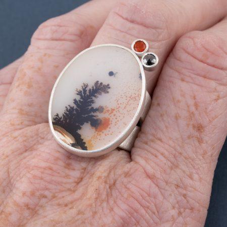Dendritic agate ring on finger