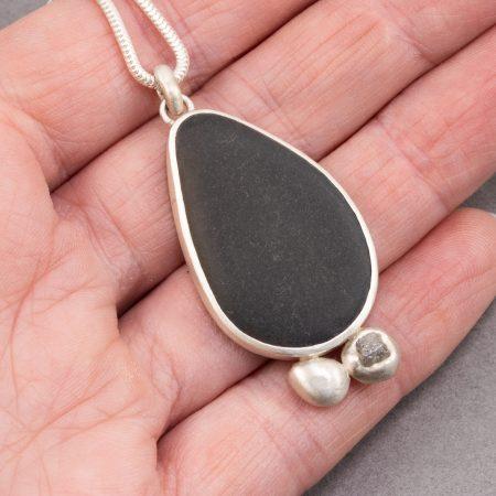 Beach pebble and raw diamond pendant in hand