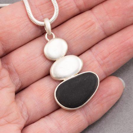 Beach pebble pendant in hand