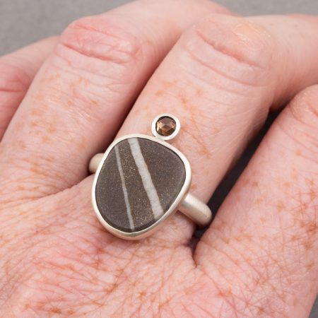 Beach pebble and brown diamond ring worn on hand