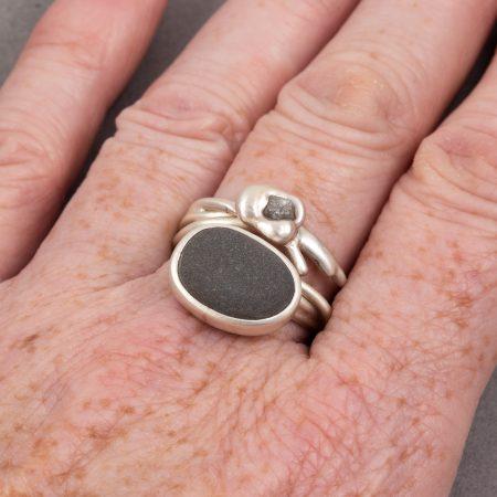 Beach pebble and grey raw diamond ring worn on hand