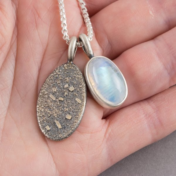 Rainbow moonstone and textured silver pendants in hand