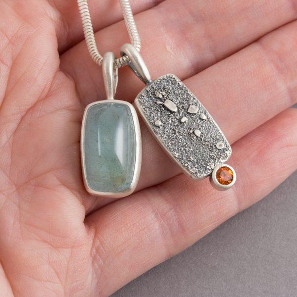 Aquamarine and orange topaz duo pendants in hand