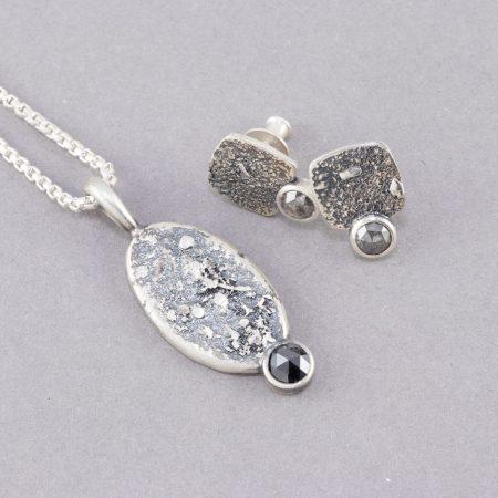 Group photo of a black diamond pendant and grey diamond stud earrings
