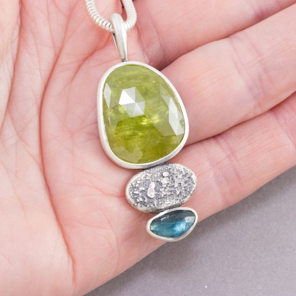 Sphene pendant with blue tourmaline in hand