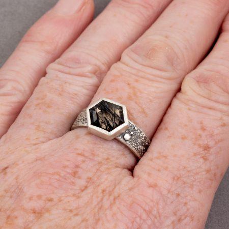 Tourmalinated quartz ring worn on finger