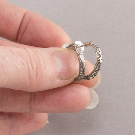 Textured sterling silver hoop earrings held between fingers