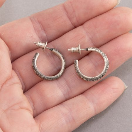 Textured sterling silver hoop earrings in palm of hand