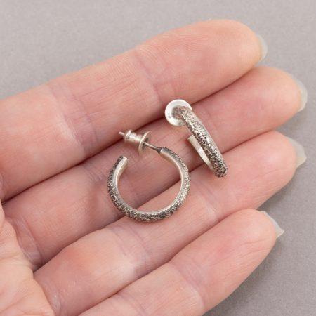 Textured sterling silver hoop earrings in hand